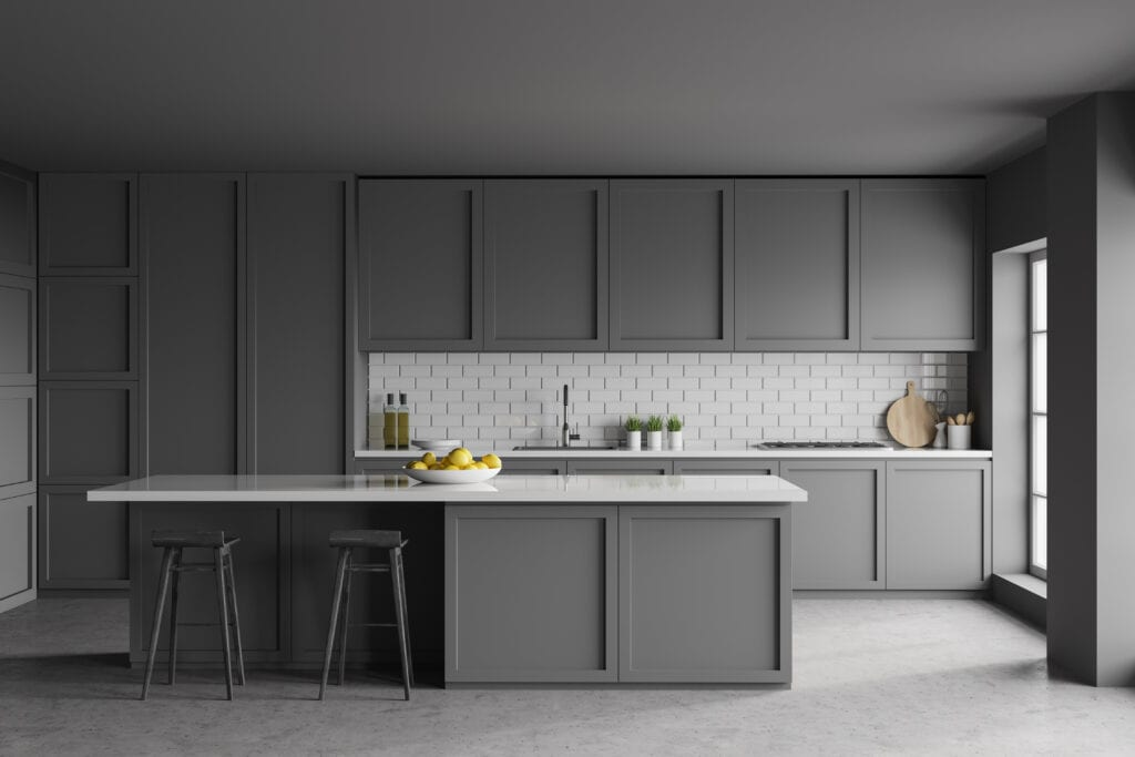 Interior of modern kitchen with dark gray and brick walls, concrete floor, grey countertops and cupboards and bar with stools. 3d rendering