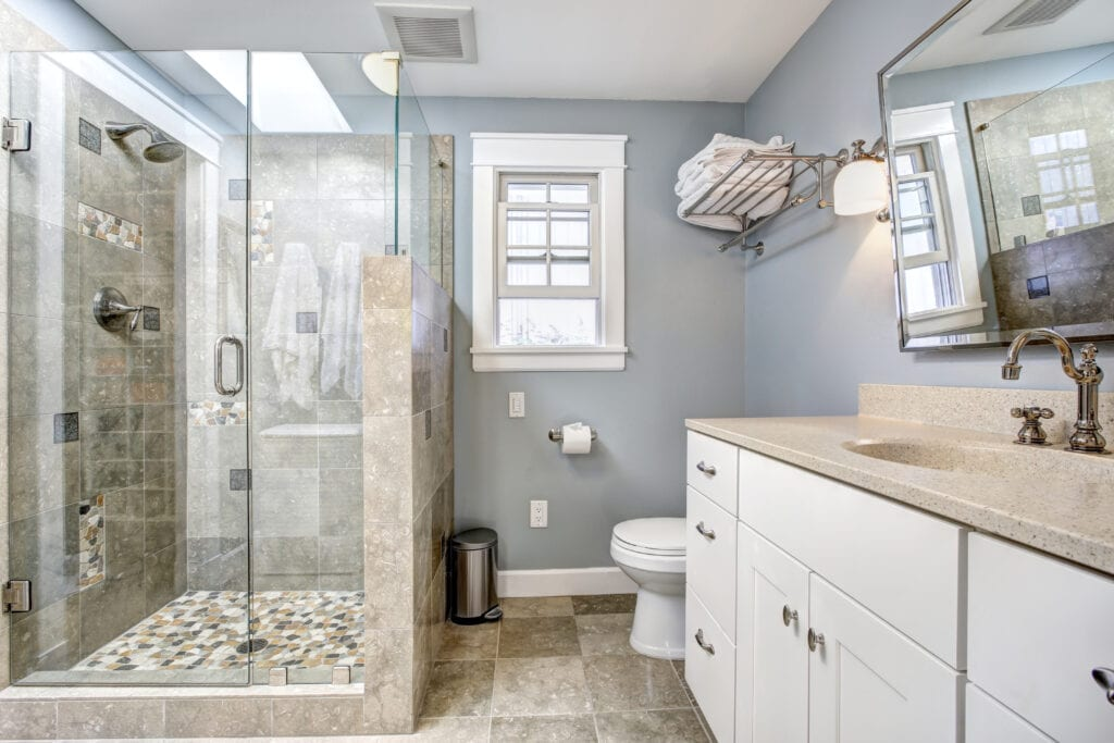 Light blue modern bathroom interior with glass door shower and white cabinet with  mirror