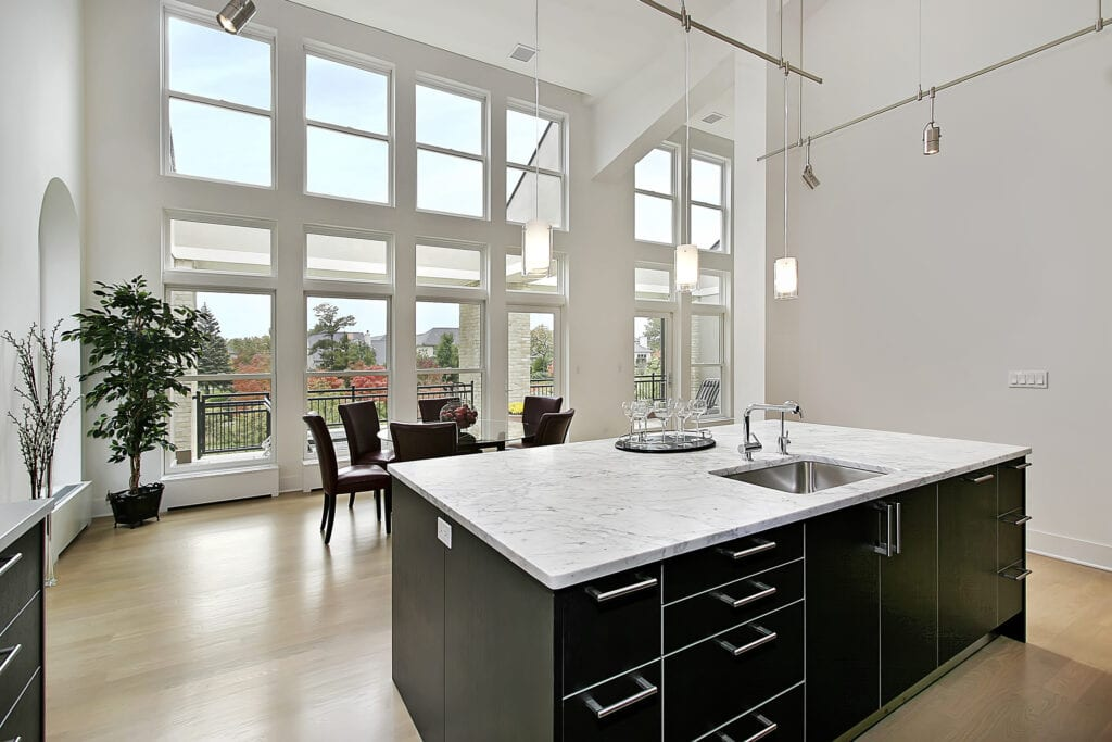 Modern kitchen in condominium with two story windows